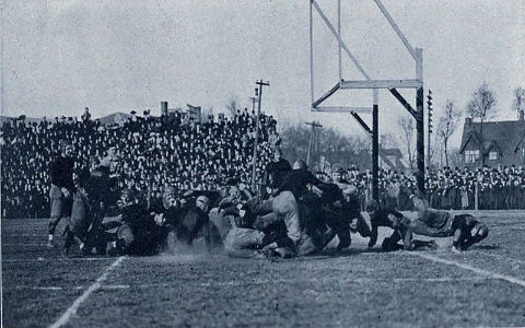 An old black-and-white shot of a college football game in progress, with a large crowd watching.