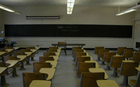 A shot from the back of a darkened classroom featuring rows of empty desks.
