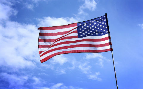 An American flag on a pole, waving in the wind against a bright blue sky.