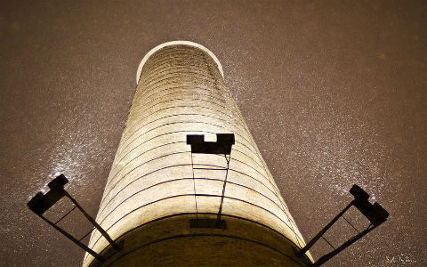 A close low angle shot of a concrete pillar with lights attached to it supporting a roof.
