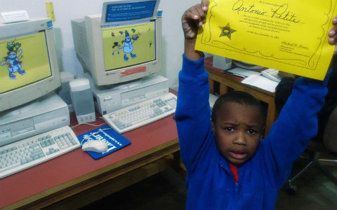 A young boy with short curly black hair and a blue sweater holding a yellow certificate of achievement above his head in triumph, in front of two school computers.