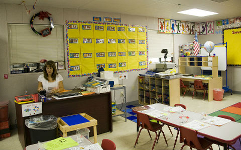 A young female teacher with shoulder length light brown hair preparing lesson plans in an empty classroom.