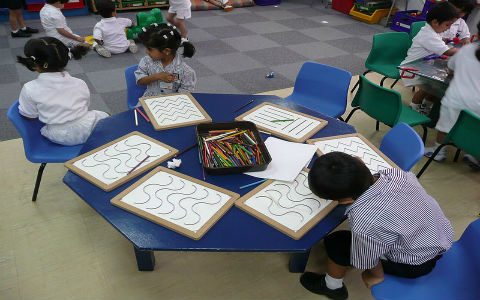 Three kindergarten children sitting at a hexagonal blue table working on drawing straight and wavy lines.