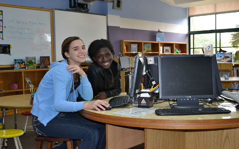 A teenage girl with straight blonde hair working with a teenage girl with short black hair at a library computer.