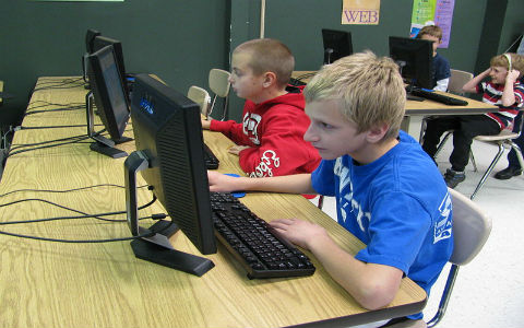 Two middle-school-aged students at the front of a computer lab class, deeply engaged in their work.