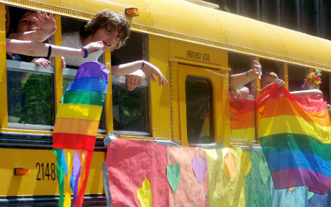 A number of children poking heads and arms out of the windows of a yellow school bus to wave rainbow flags.