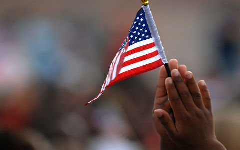 A small American flag being held by the clasped palms of a young child's hands, with a blurred crowd in the background.
