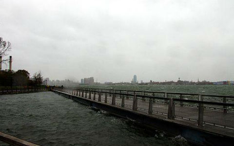 A shot of a wooden bridge extending over turbulent water, with New York City visible in the far distance under dark skies.