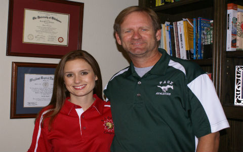 A young woman with long straight brown hair in a red track suit smiling beside her father in a green jersey in front of a bookshelf in their house.