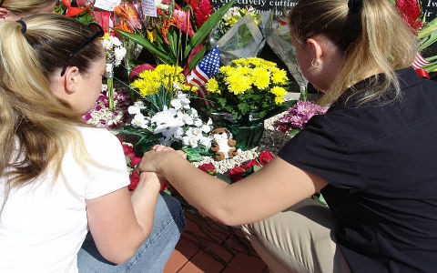 Two girls with long blonde hair sit on cobblestones hand-in-hand in front of flowers left in memoriam.