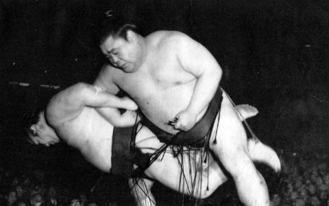 A black and white shot of two sumo wrestlers falling over together, arms linked.