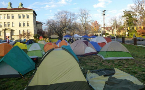 A large number of tents of various colors pitched on the lawn in front of a stately building.