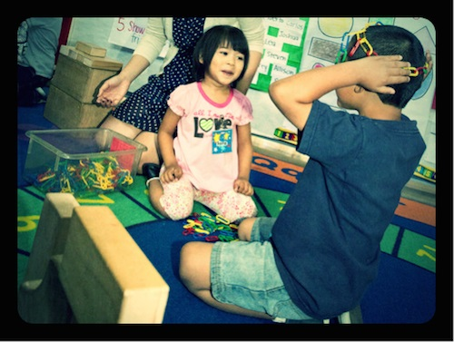 A Polaroid-style shot of a young boy and girl playing with blocks and plastic colored chain links.