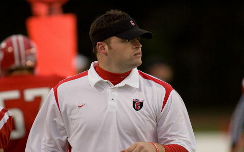 A middle-aged man with short brown hair, a black visor, and a white polo shirt looks to the left at a football game in front of a team in red uniforms.