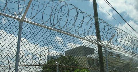 A close shot of a chain link fence with barbed wire on top, with an institutional building in the background.