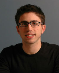 A close head shot of a young man with brown hair and black framed glasses smiling on a grey background, wearing a black turtleneck.