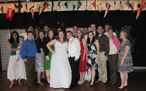 A large group of young and middle-aged people standing behind a smiling bride and groom, underneath a string of colored pennants.