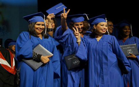 A group of young women with black and brown hair smiling at their graduation, posing in blue gowns and hats.