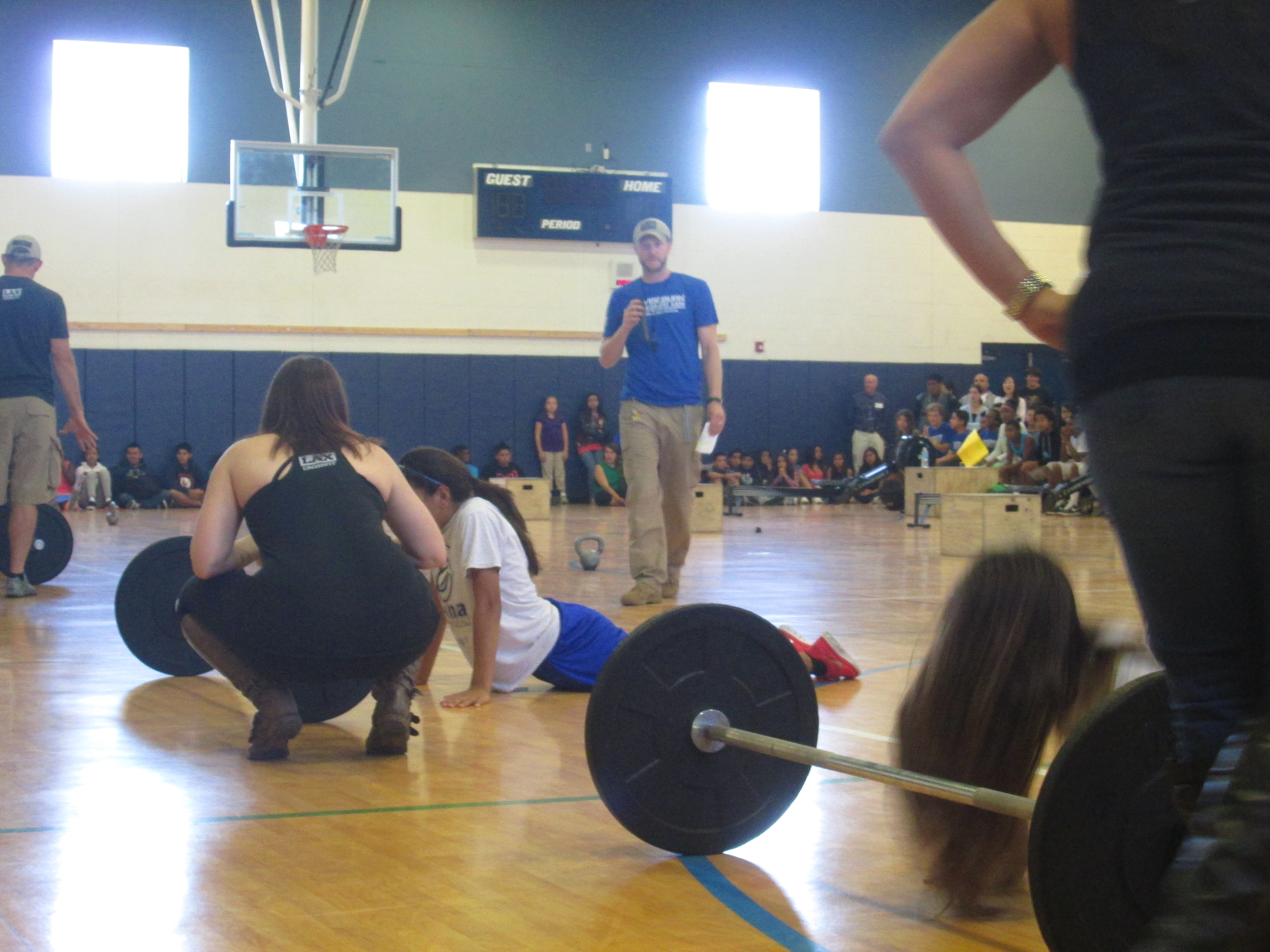 A floor-level shot of a basketball court, on which students are doing push-ups in front of large barbell weights, each being supervised by a female instructor. Students line the outside walls of the court, and a young male gym teacher in a blue t-shirt is walking towards the camera, wearing a whistle.