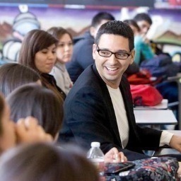 A young teacher with short black hair, black framed glasses and a black blazer smiling in the middle of a room full of students.