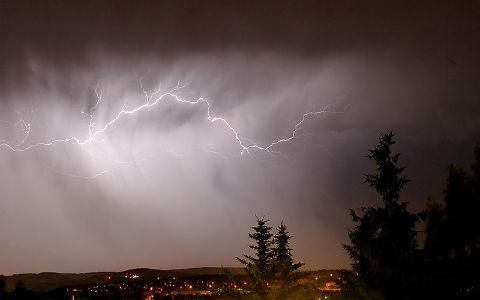A lightning bolt streaks across a cloudy sky, above a town in a valley.