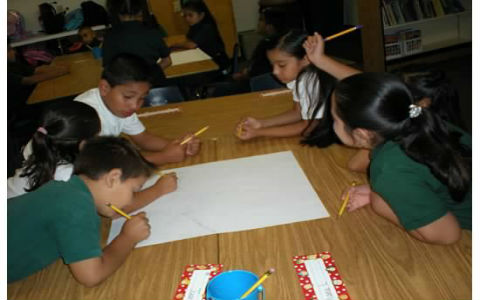 A group of elementary students all holding pencils, working together on a single large piece of paper.