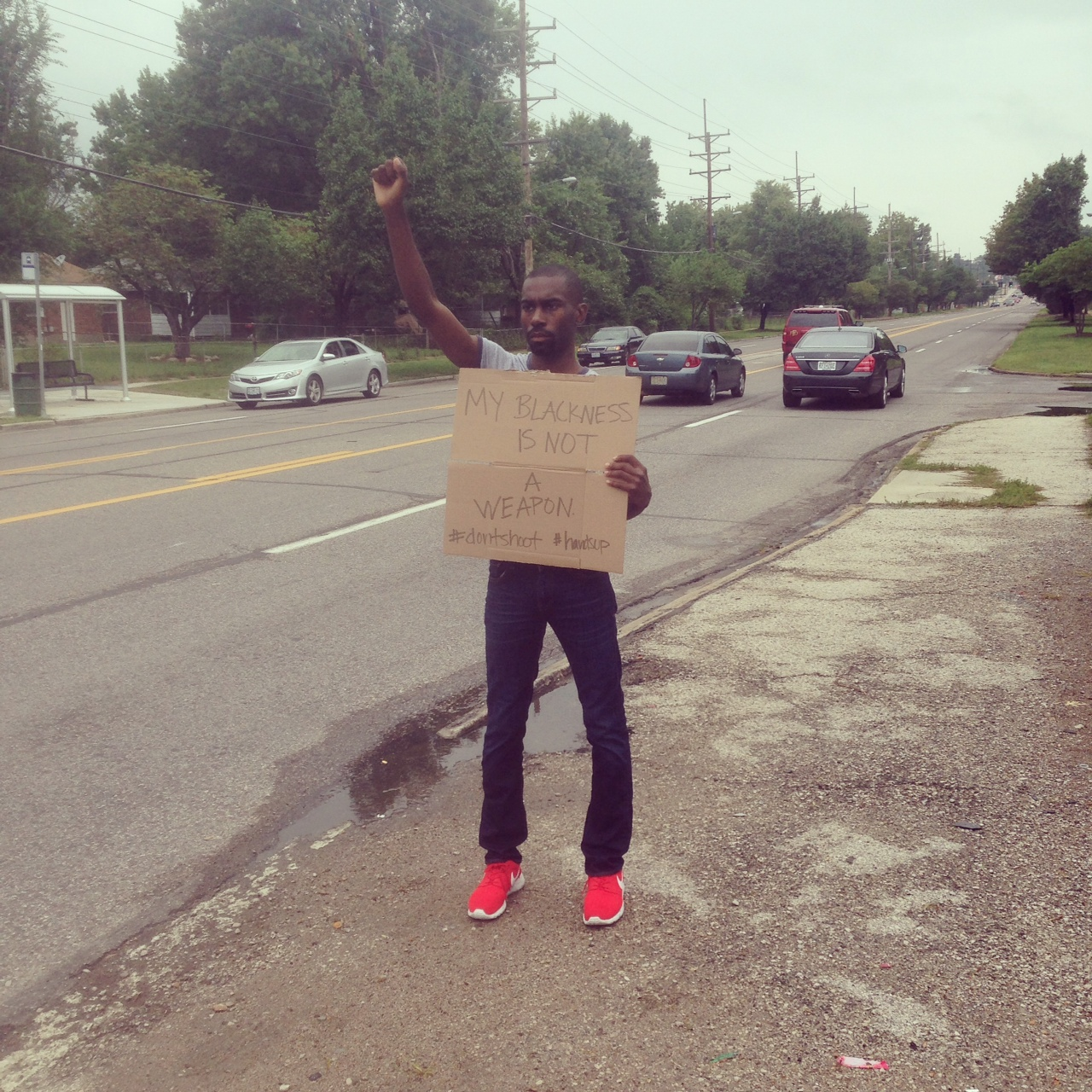 "A young man standing by the side of the road with one arm raised, holding a sign that says ""My blackness is not a weapon."""