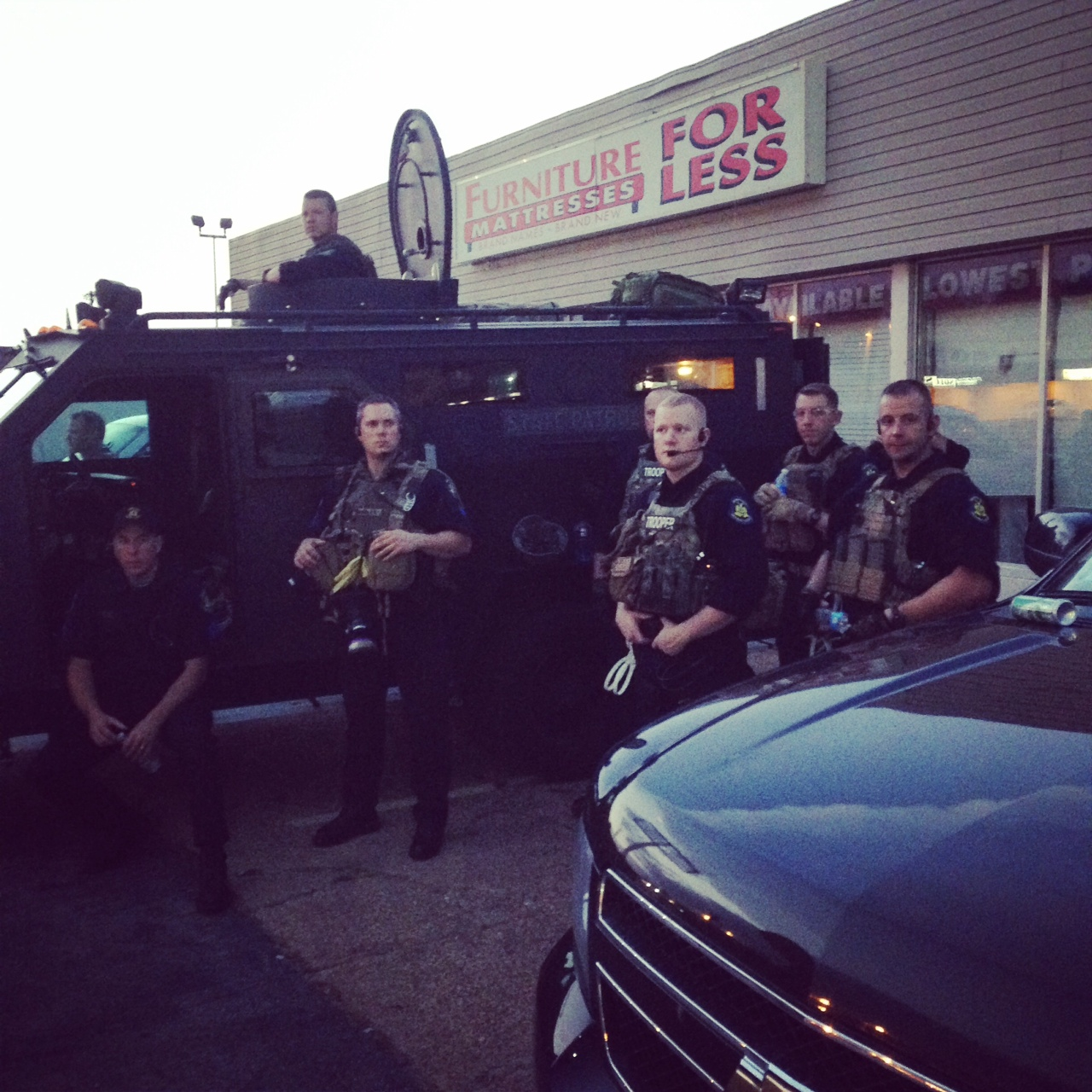 A grainy photo of a team of state troopers around a tactical assault vehicle, in a furniture store parking lot.