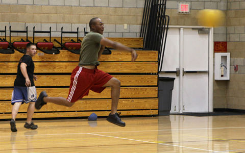 A man in a green t-shirt and red shorts throws a yellow ball in a school gym as his teammate looks on.