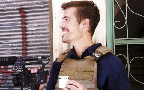 A young man with short red hair and a mustache, wearing a brown vest and holding a cup of espresso smiling behind a video camera with a microphone attached.