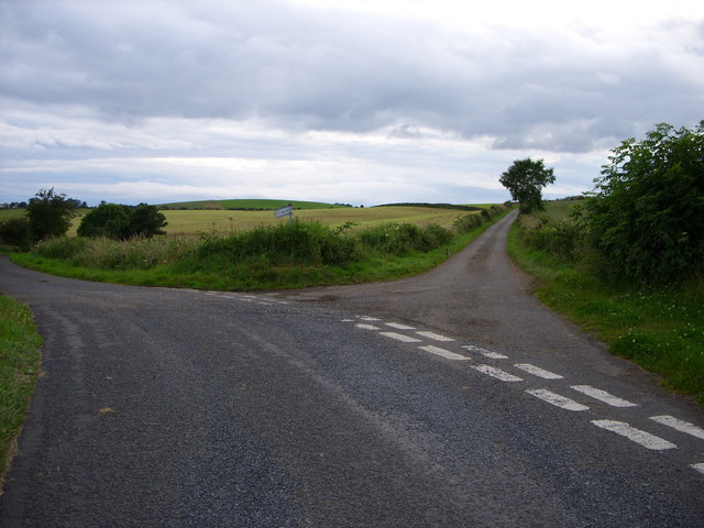 A fork in a gravel road in the country, with some trees visible far in the background.