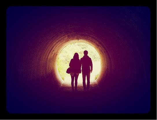 A young man and a young woman walking arm-in arm out of a dark tunnel and into the sunlight.