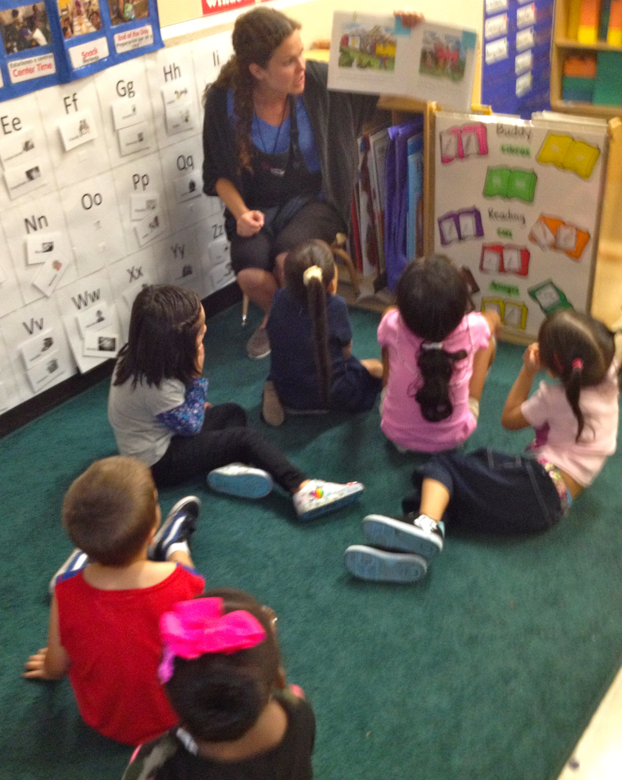 A young teacher with long wavy brown hair helping her class of elementary students read a book.