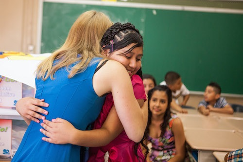 A female teacher in a blue dress with long blonde hair being hugged by a female student in pink.