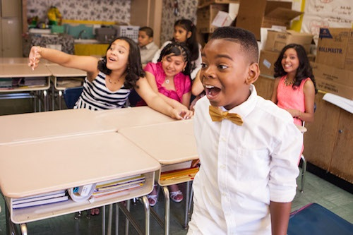 An elementary school student in a dress shirt and bow tie standing in a classroom, mouth agape in surprise.