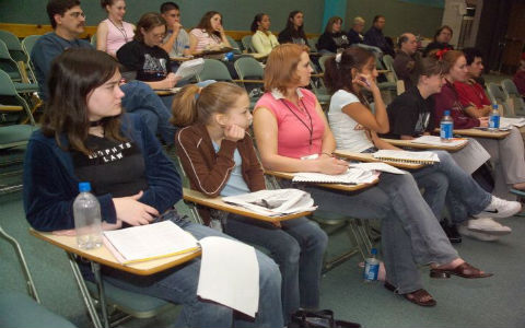 A class of high school students with notebooks out, listening intently to a lecture.