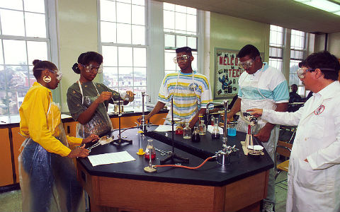 Six high school students with dark brown hair stand around a hexagonal black lab bench conducting science experiments, wearing safety goggles.