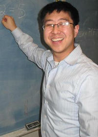 A young male teacher with straight black hair smiling while writing a math problem on the blackboard.