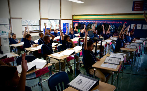 A classroom full of young students wearing dark blue shirts with their hands all up.