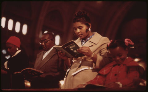 A low angle shot of a family wearing winter coats standing a reading from prayer books in a large church.
