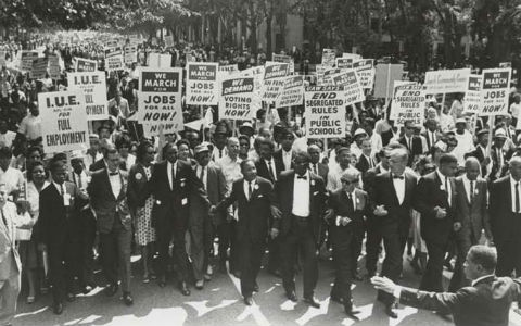 A black and white shot of Martin Luther King's March on Washington, featuring men in suits holding signs demanding jobs.