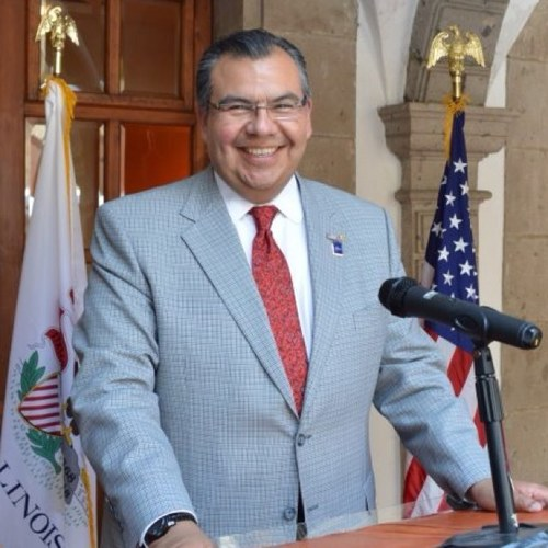 A middle-aged man with slicked hair smiles from a podium, wearing a blue blazer, white shirt, and red tie, with an American flag and another flag in the background.