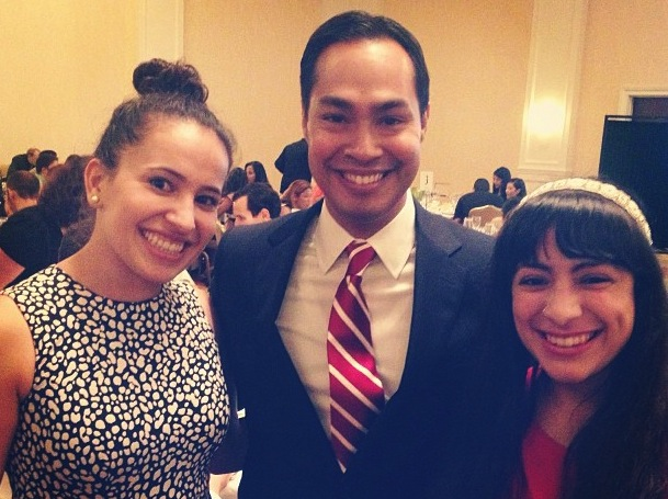 A middle-aged man with a receding hairline smiling at a party, beside two younger women, wearing a black blazer, a white dress shirt, and a red and white striped tie.
