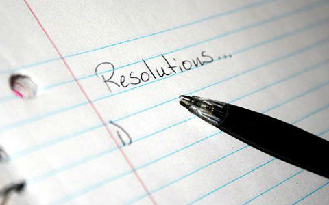 "A close shot of blue lined writing paper with a black pen resting on it and the word ""resolutions"" written at the top."