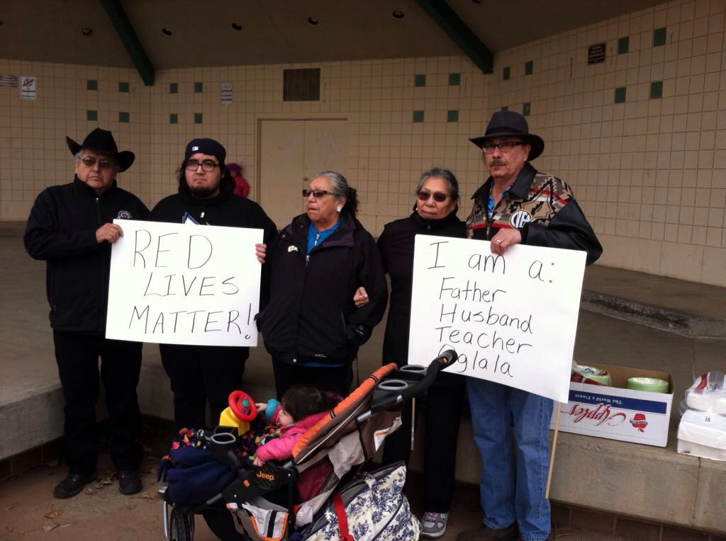 """Four middle-aged and elderly teachers wearing black in front of a school, holding white protest signs, with one reading """"Red Lives Matter."""""""