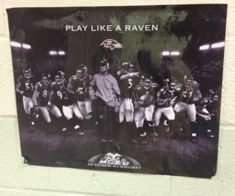 "A shot of a black and white poster of a football team with white text reading ""play like a raven."""