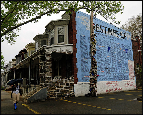 "A side view of an urban townhouse, covered entirely in a blue mural with black text saying ""Rest in Peace"" and covered with the names of the dead."