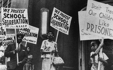 An old black-and-white photograph of a group of African-American adults and children holding signs protesting school segregation.
