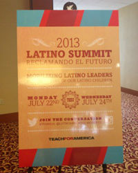 A picture of an orange and red sign advertising the 2013 Latino Summit, with most of the content obscured by glare.