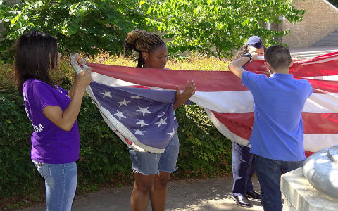 Four young teenage students folding a large American flag in front of their school.